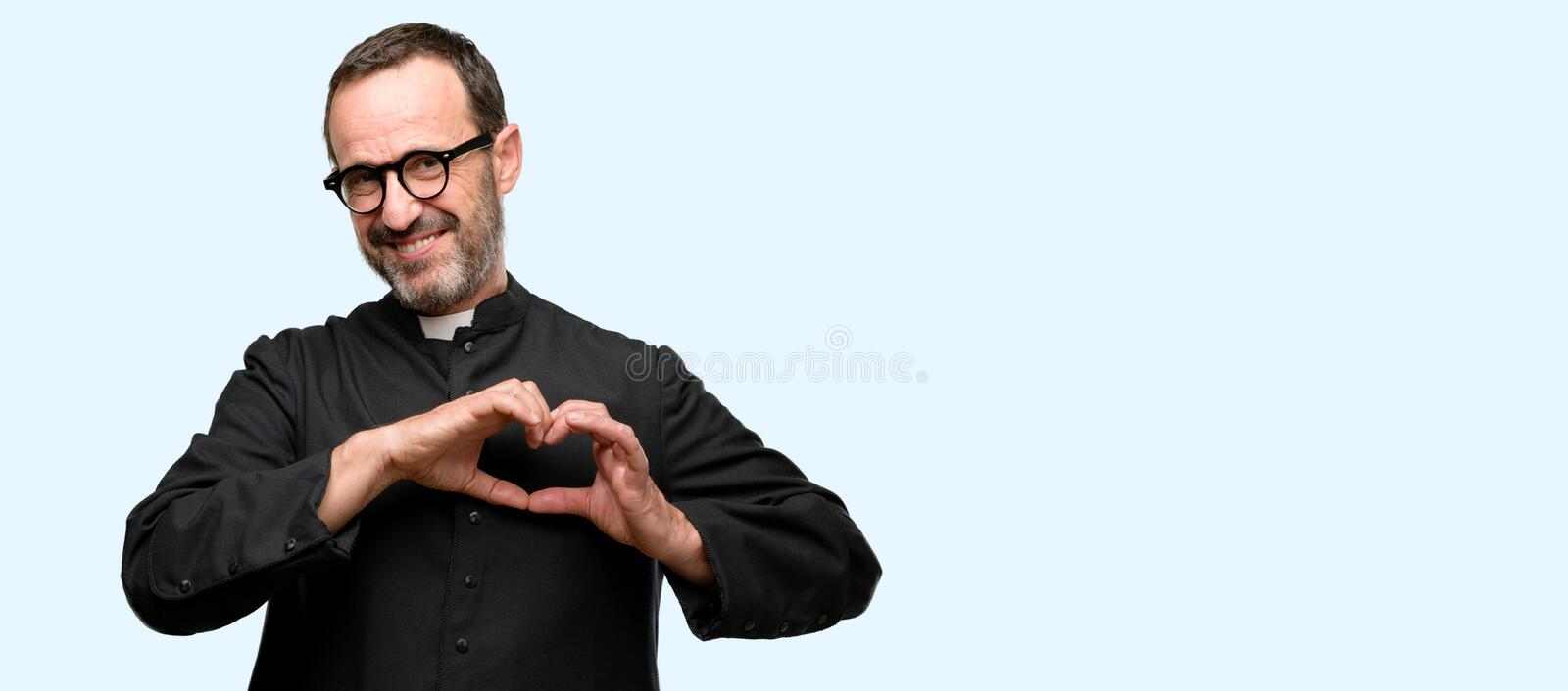 Handsome senior man isolated over blue background. Priest religion man happy showing love with hands in heart shape expressing healthy and marriage symbol stock images