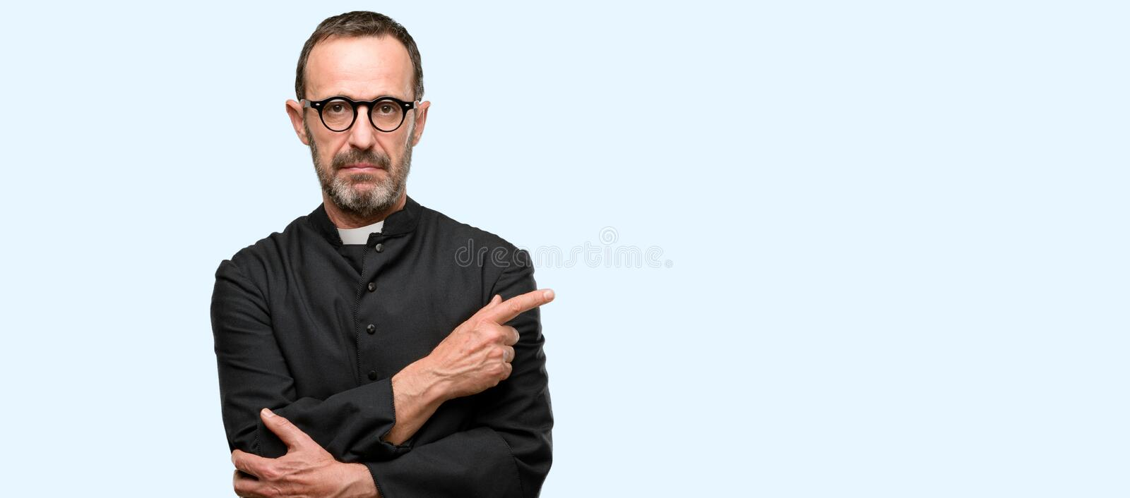 Handsome senior man isolated over blue background. Priest religion man pointing away side with finger isolated over blue background royalty free stock photos