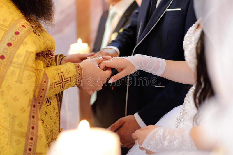 Priest at Wedding Ceremony. Priest holding bride and groom's hands royalty free stock image