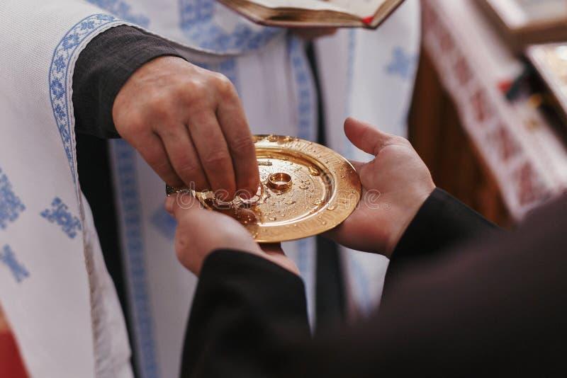 Priester, der goldenen Ehering von der Platte nimmt Hochzeitsehestand lizenzfreie stockfotografie