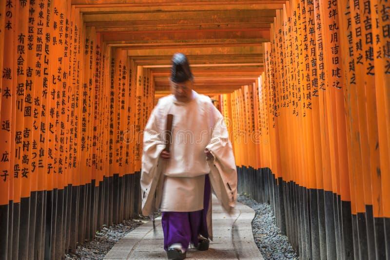 Priester die door Torii-Poorten, het Heiligdom van Fushimi Inari, Kyoto lopen stock afbeeldingen