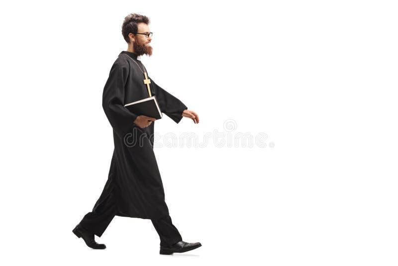 Priester die een bijbel en het lopen houden royalty-vrije stock afbeeldingen