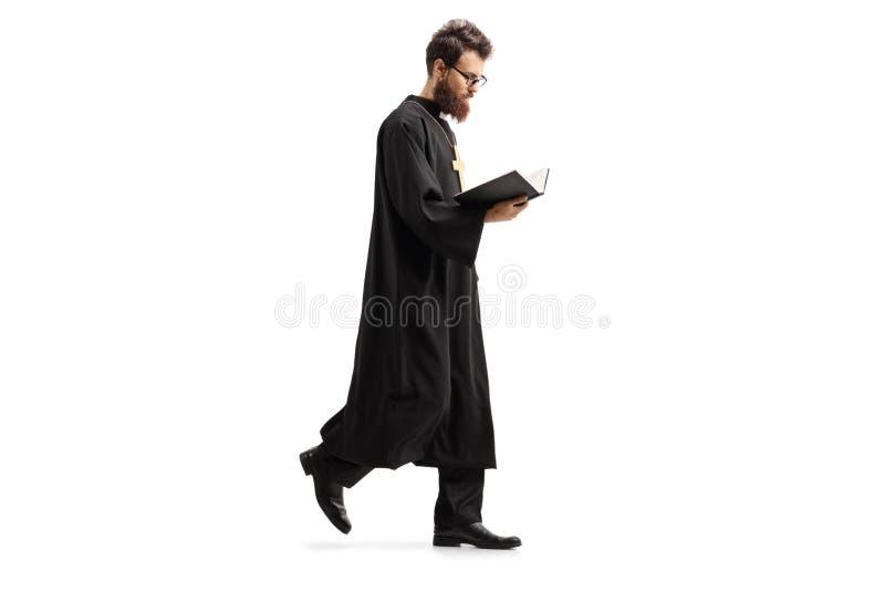 Priester die en de Bijbel lopen lezen stock fotografie