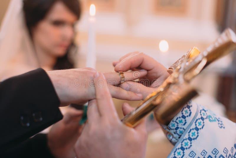 Priester, die heilig kruis de houden zettend op ringsbruidegom dient de kerk in royalty-vrije stock foto