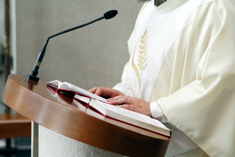 Priester die open hulstbijbel leest stock afbeeldingen