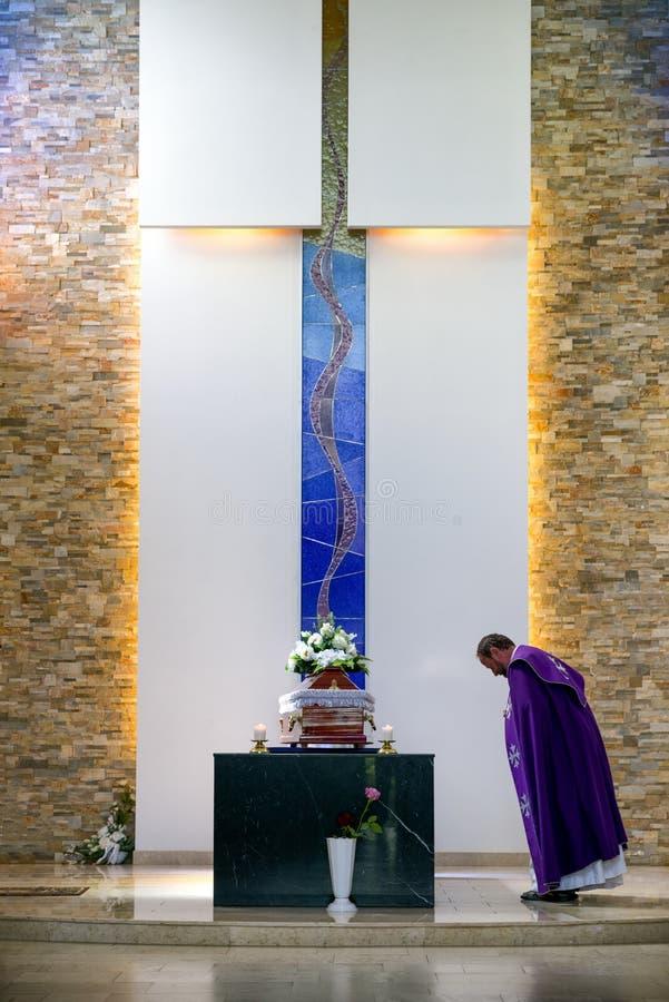 Priester en doodskist bij het rouwen ceremonie stock fotografie