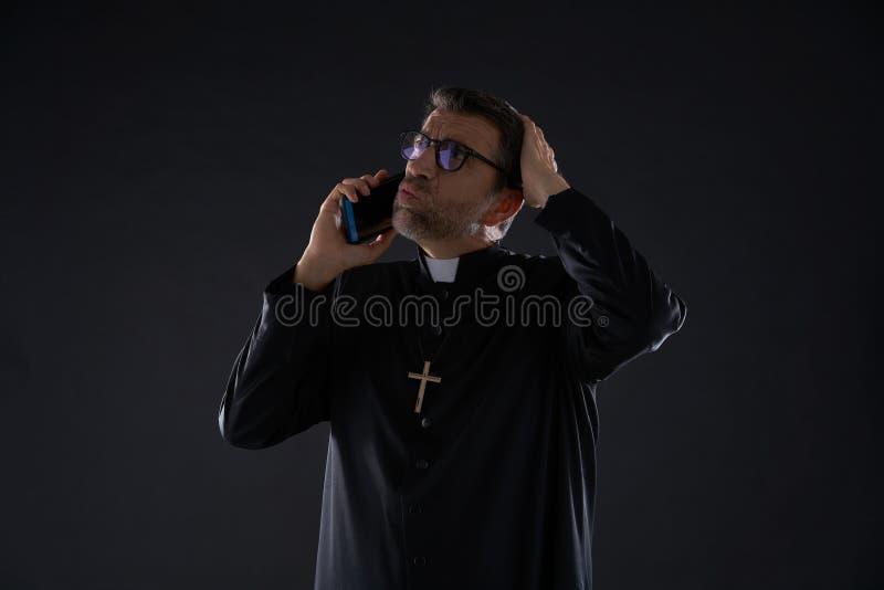 Priester het spreken smartphone grappige uitdrukking stock fotografie