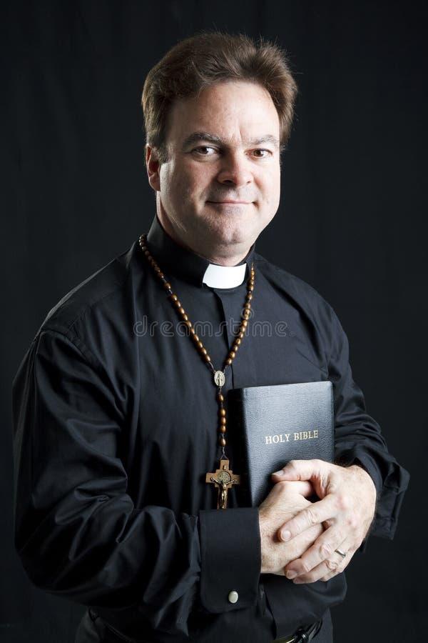 Priester mit Rosenbeet und Bibel stockfotografie