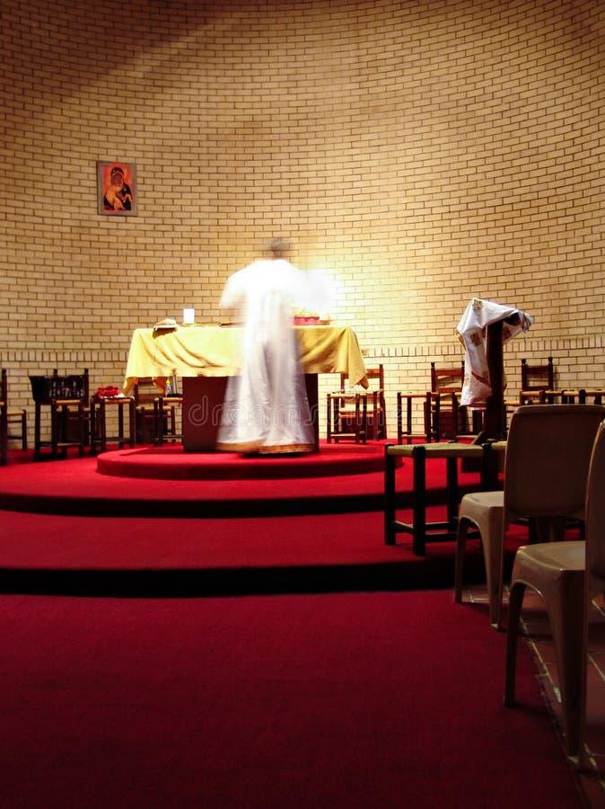 Priester op het altaar stock fotografie