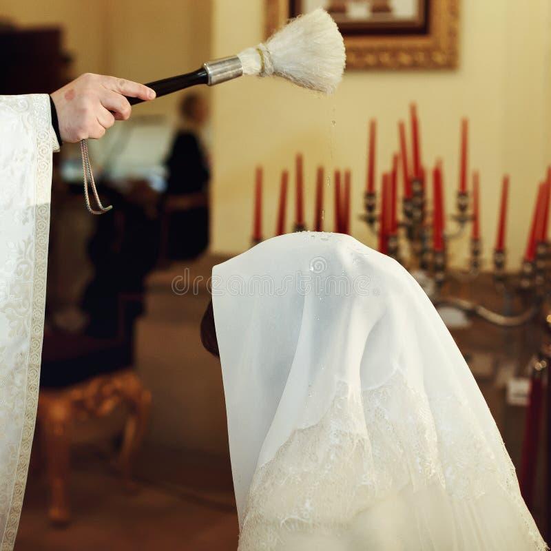 Priester segnen Braut, während sie auf Knien in der Kirche steht stockfoto