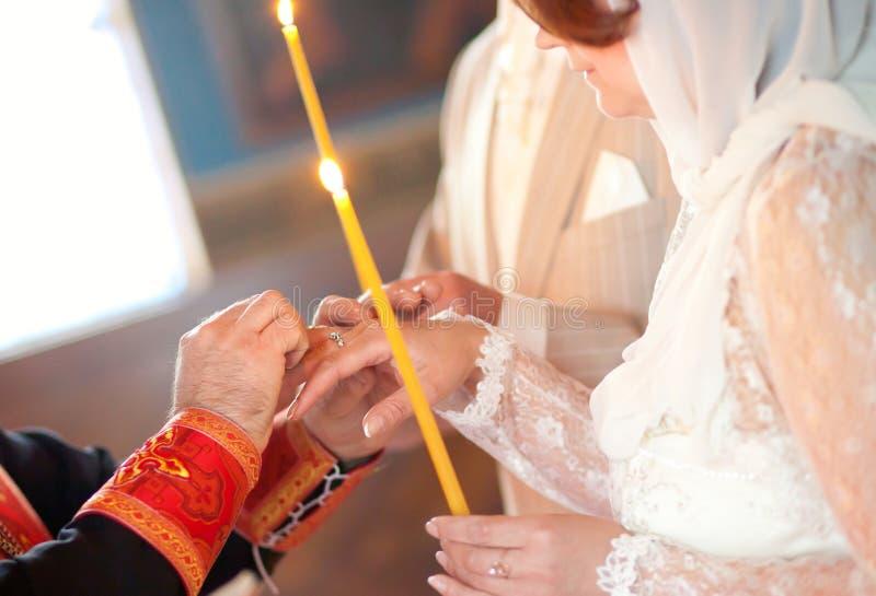 Priester setzt Ring auf Finger der Braut lizenzfreie stockbilder