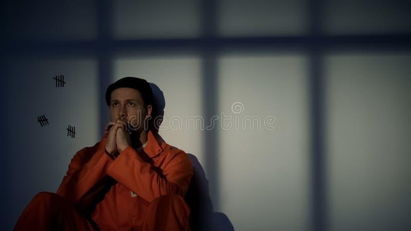 Prigioniero caucasico: pregare, sentirsi colpevole di crimini, chiedere pietà fotografia stock