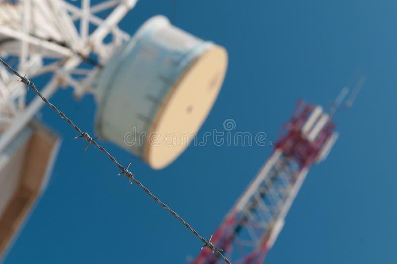 Prikkeldraad met communicatie torens en blauwe hemel op achtergrond royalty-vrije stock foto