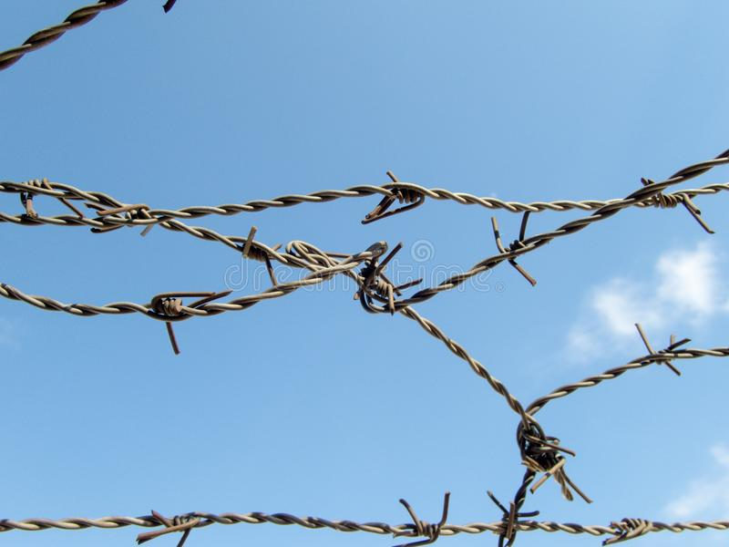 Prikkeldraad op het blauwe hemel verloren concept van het de vluchtelingskamp van de vrijheidsopsluiting royalty-vrije stock foto