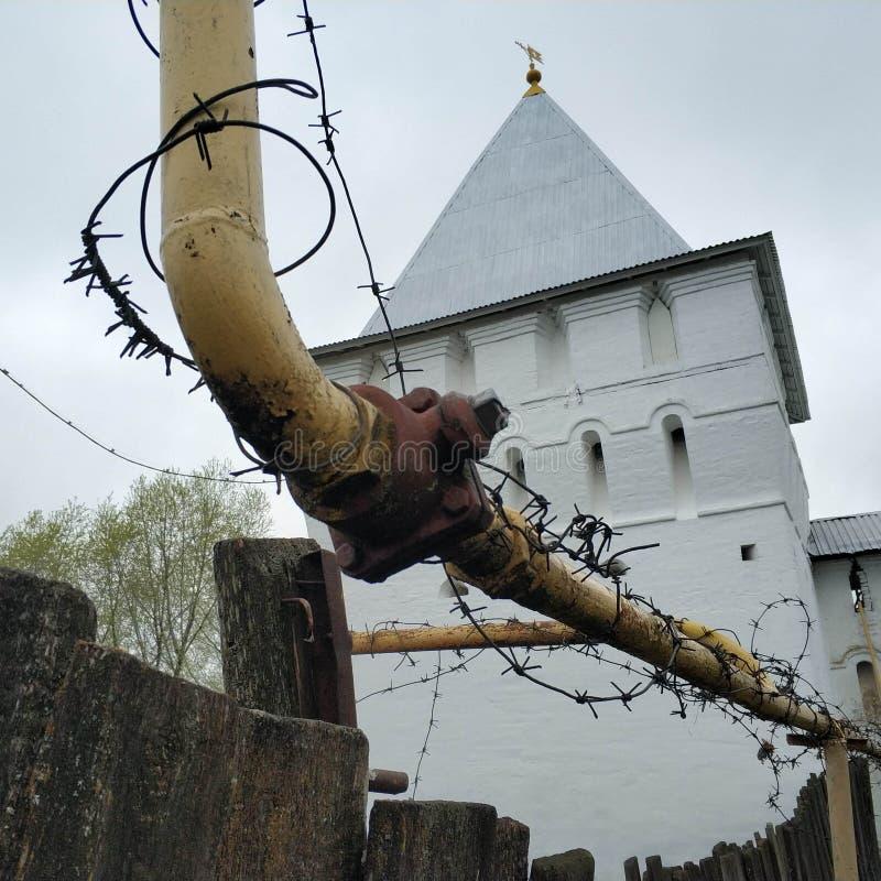 Prikkeldraad over een gele pijp wordt uitgerekt die Achter haar is een kerk Oude witte baksteenkerk stock foto