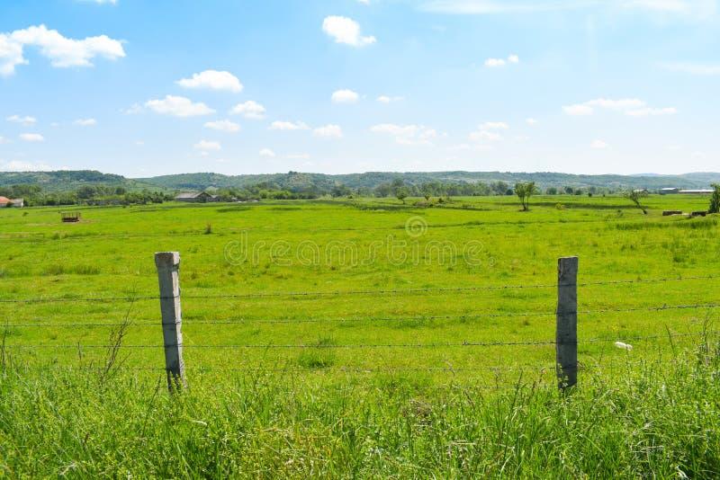 Prikkeldraadomheining in de mooie groene vallei in een zonnige de zomerdag met heldere blauwe hemel en witte wolken royalty-vrije stock afbeelding