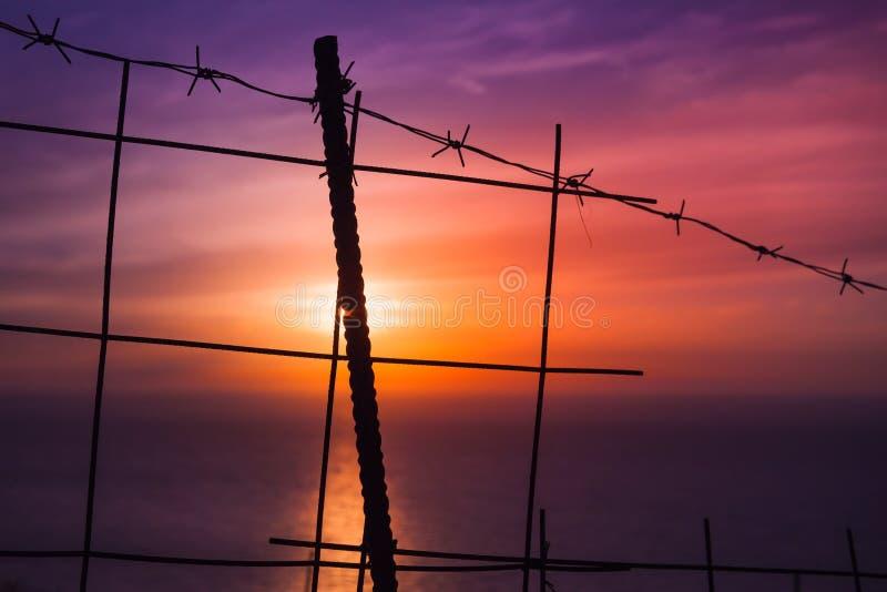 Prikkeldraadomheining met kleurrijke zonsondergang stock foto's