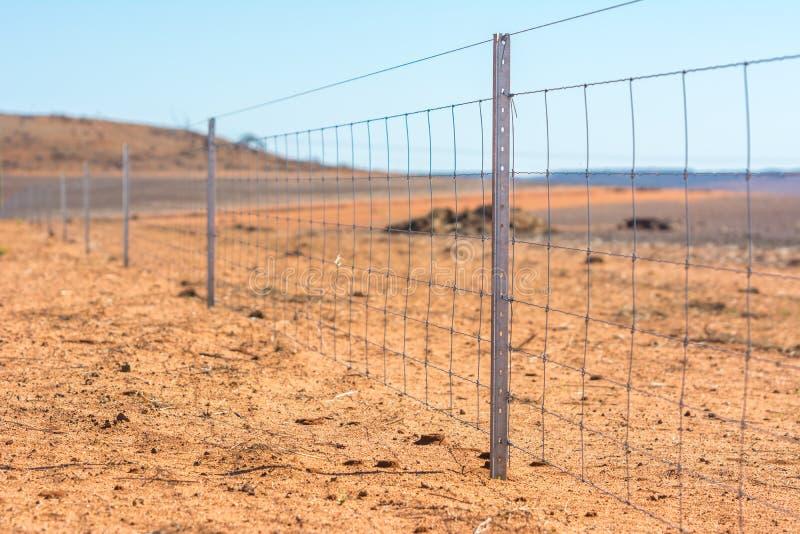 Prikkeldraadomheining op droog land in West-Australië stock foto
