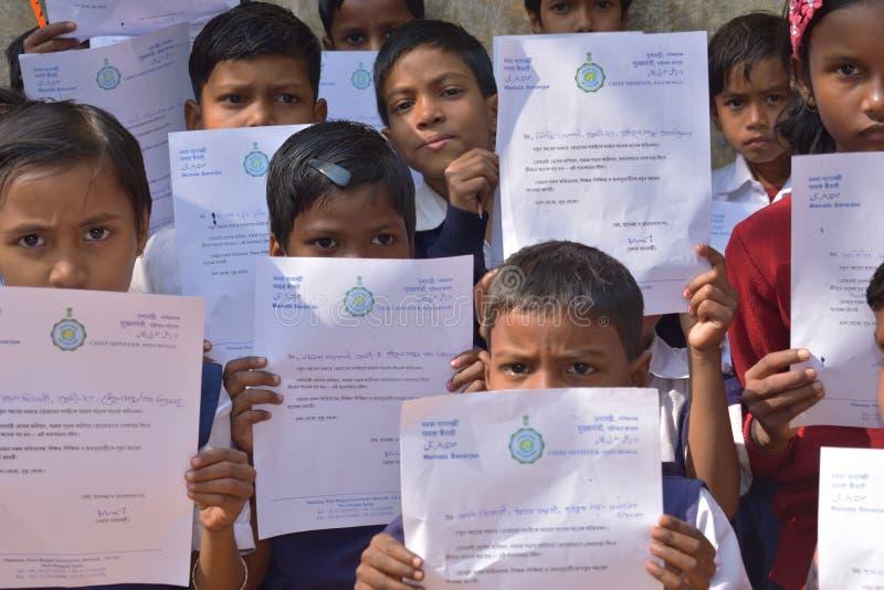 Primärstudenten zeigt ihre Grußbriefe, die ihnen vom Hauptminister von Westbengalen geschickt wurden lizenzfreie stockfotografie