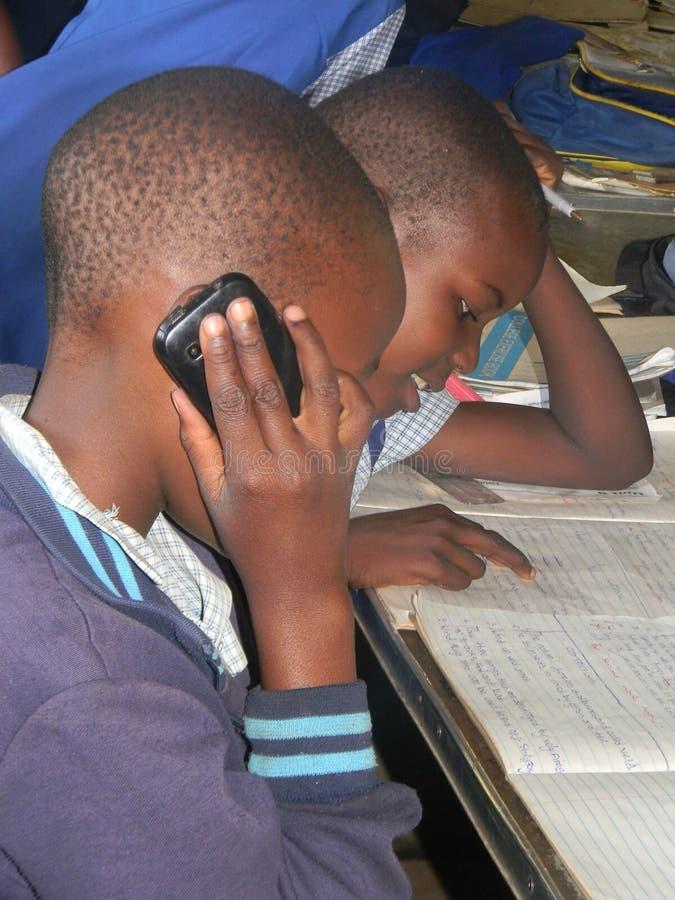 Primärschulmädchen, das über Mobiltelefon im Klassenzimmer spricht stockfotografie