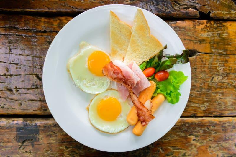 Prima colazione americana con le uova, bacon, pane tostato, prosciutto, salsiccia, vegeta immagini stock