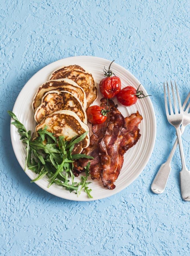 Prima colazione americana tradizionale - il bacon croccante, pancake con sciroppo d'acero, ha arrostito i pomodori, rucola Su una fotografia stock libera da diritti