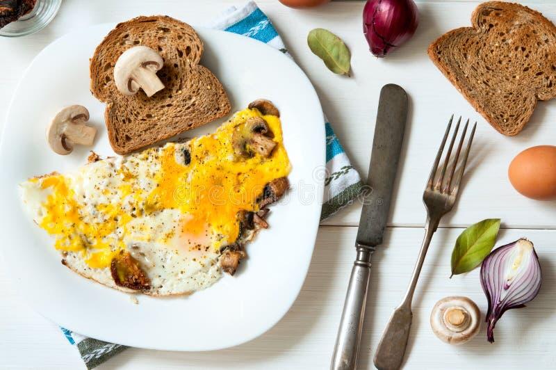 Prima colazione calorosa: piatto delle uova fritte e dei funghi con pane sulla superficie bianca della tavola, vista piana superi immagini stock libere da diritti