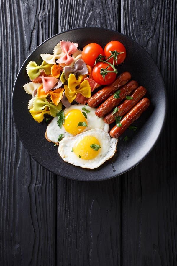 Prima colazione calorosa: uova fritte, salsiccie, pasta del farfalle e tomat fotografie stock