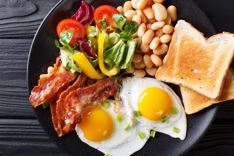 Prima colazione casalinga inglese: uova fritte con bacon, fagioli, pane tostato immagini stock libere da diritti
