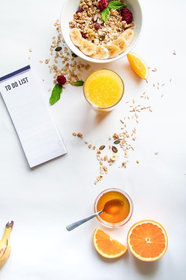 Prima colazione con la farina d'avena e fare lista su fondo bianco fotografia stock libera da diritti