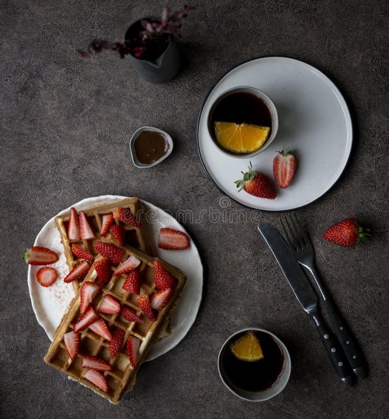 Prima colazione con le cialde del Belgio con la fragola ed il cioccolato a fondo scuro Concetto dello stile di vita saporito immagine stock libera da diritti
