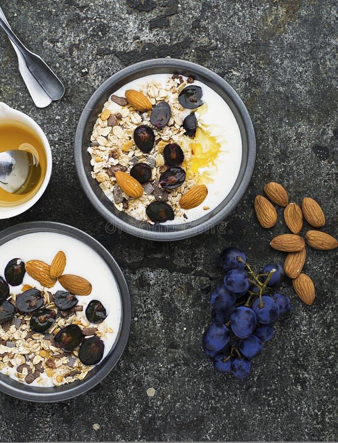 Prima colazione dagli ingredienti stagionali sani: granola, fiocchi, miele, uva scura, mandorle in un pial grigio del servizio su fotografia stock libera da diritti