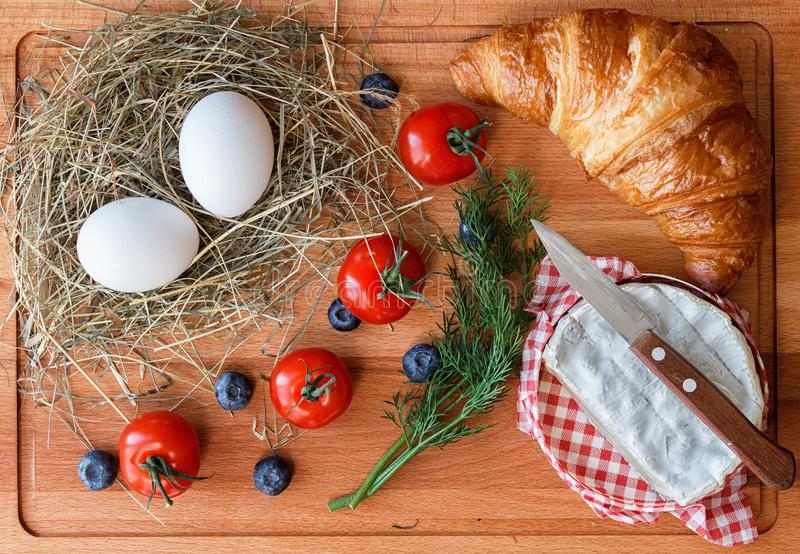 Prima colazione del paese con le uova, il formaggio ed il croissant fotografie stock