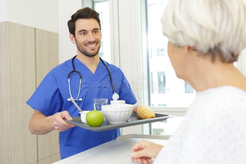 Prima colazione del servizio dell'infermiere al paziente in ospedale fotografie stock libere da diritti