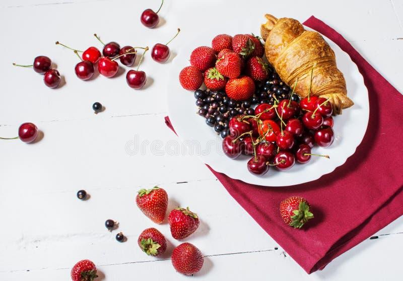 Prima colazione deliziosa con i croissant freschi e le bacche mature su fondo di legno bianco immagini stock