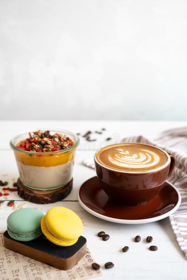 Prima colazione deliziosa sulla tavola La tazza di caff?, il budino del mango e i macarons alla tavola bianca immagini stock