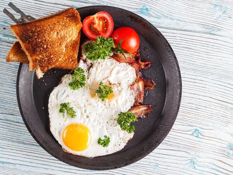 Prima colazione delle uova con il pomodoro ed il prezzemolo Fuoco selettivo fotografia stock libera da diritti