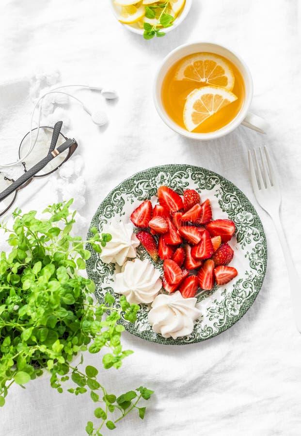 Prima colazione di estate o dessert - fragole fresche, meringa, tè verde con il limone Natura morta domestica accogliente della p fotografia stock