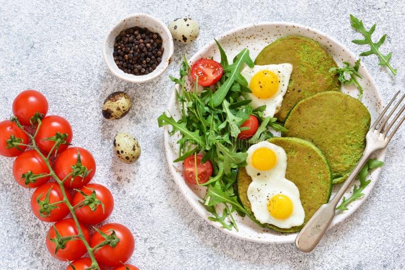 Prima colazione di mattina: pancake con spinaci, insalata e l'uovo sul tavolo da cucina fotografie stock libere da diritti
