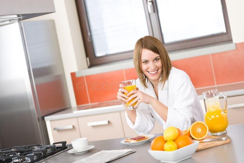 Prima colazione - donna sorridente con il succo di arancia fresco immagine stock libera da diritti