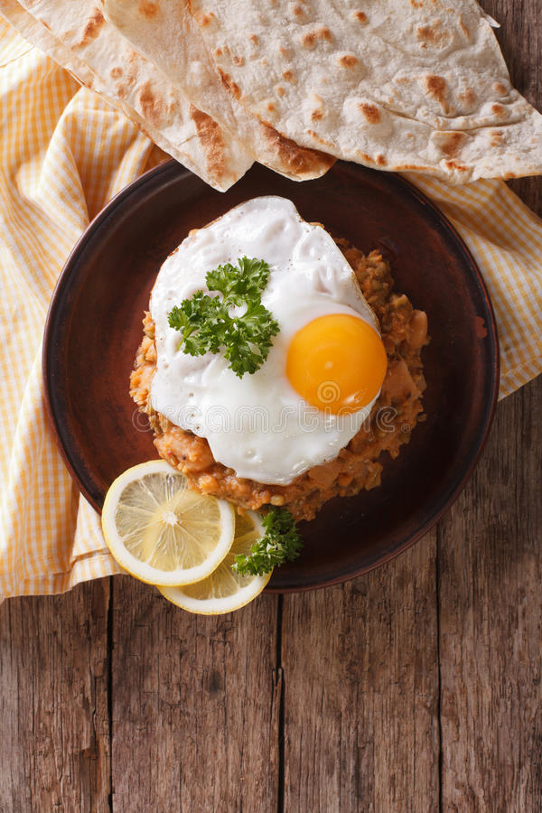 Prima colazione egiziana: medames del ful con un uovo fritto principale verticale v fotografia stock