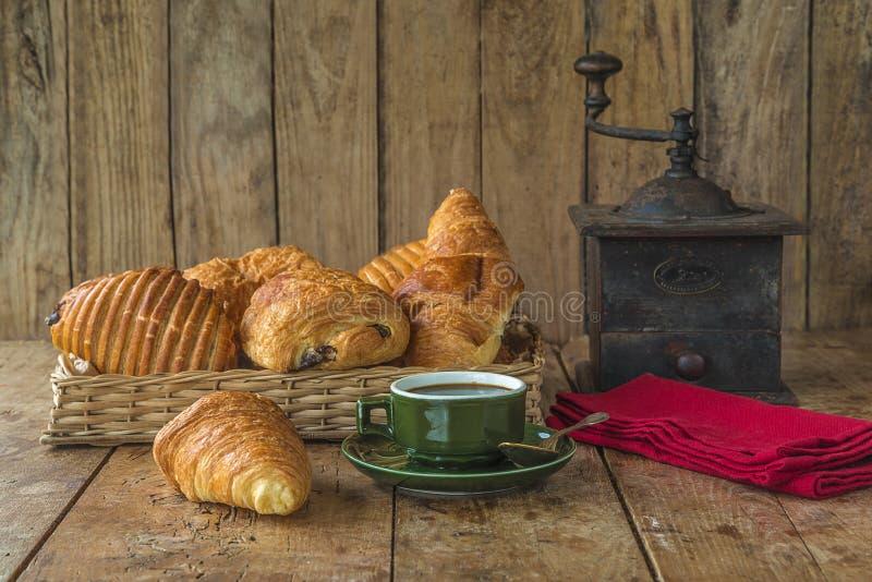 Prima colazione francese tradizionale: tazza d'annata di caffè caldo, canestro di vimini con vario dei croissant fotografia stock