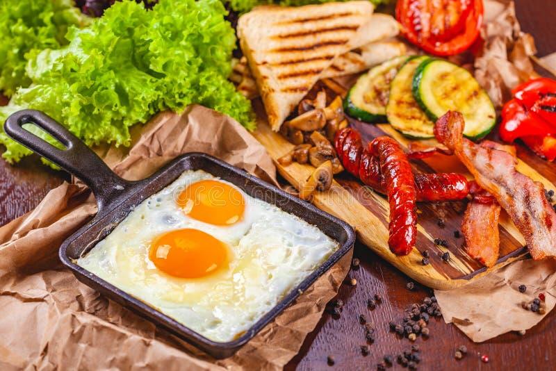 Prima colazione inglese con le uova fritte, le salsiccie, il bacon, le verdure, il pane e le spezie immagini stock libere da diritti