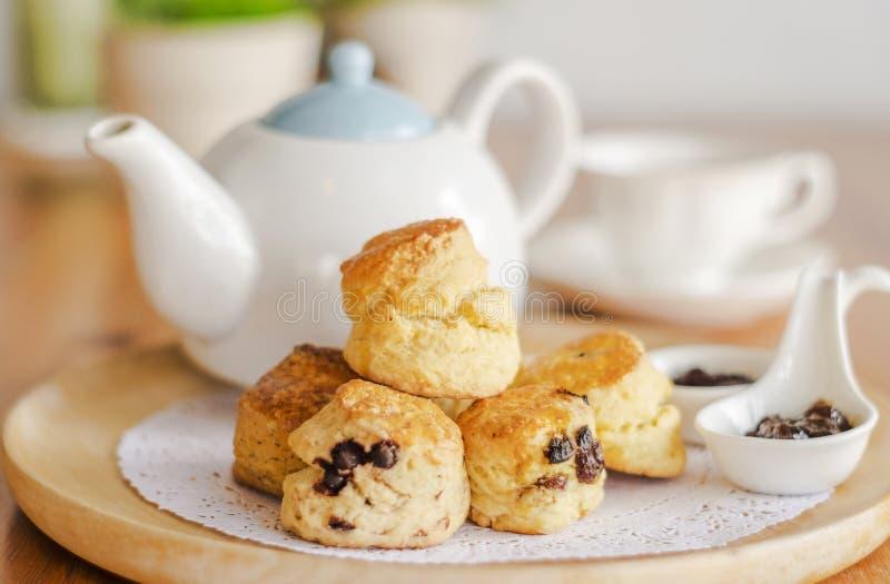 Prima colazione inglese e pausa tè focaccine al latte sulla tavola di legno con una tazza di tè fotografie stock