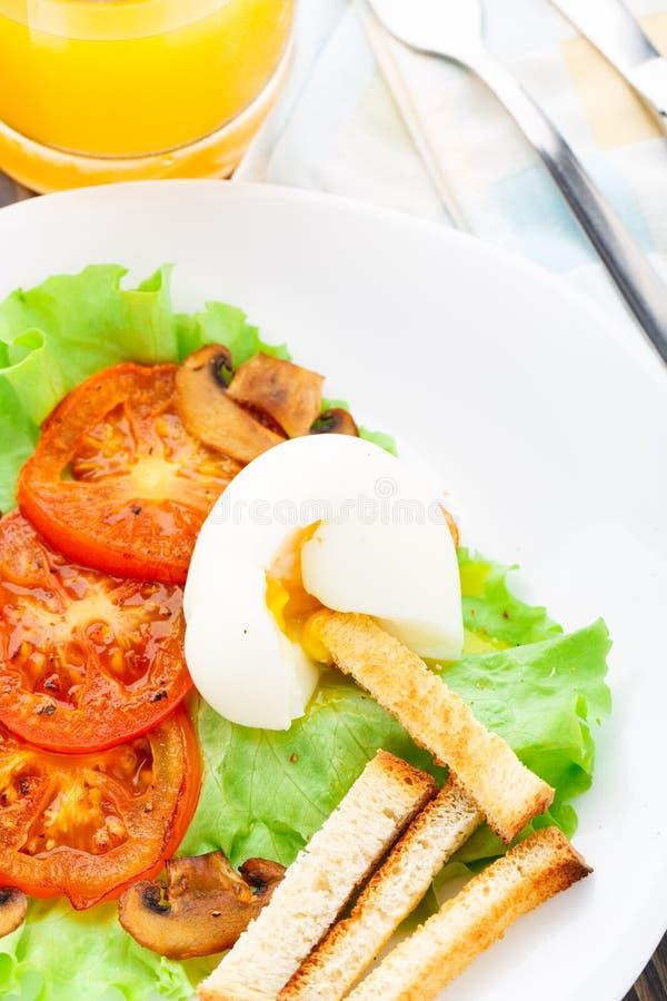 Prima colazione leggera con l'uovo molle, il pomodoro ed i crostini immagini stock