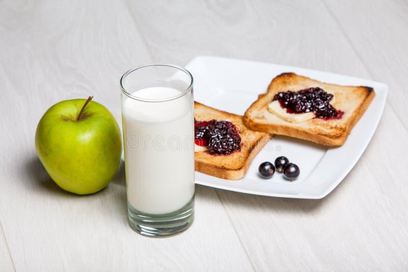 Prima colazione leggera - latte e pani tostati con inceppamento fotografie stock libere da diritti