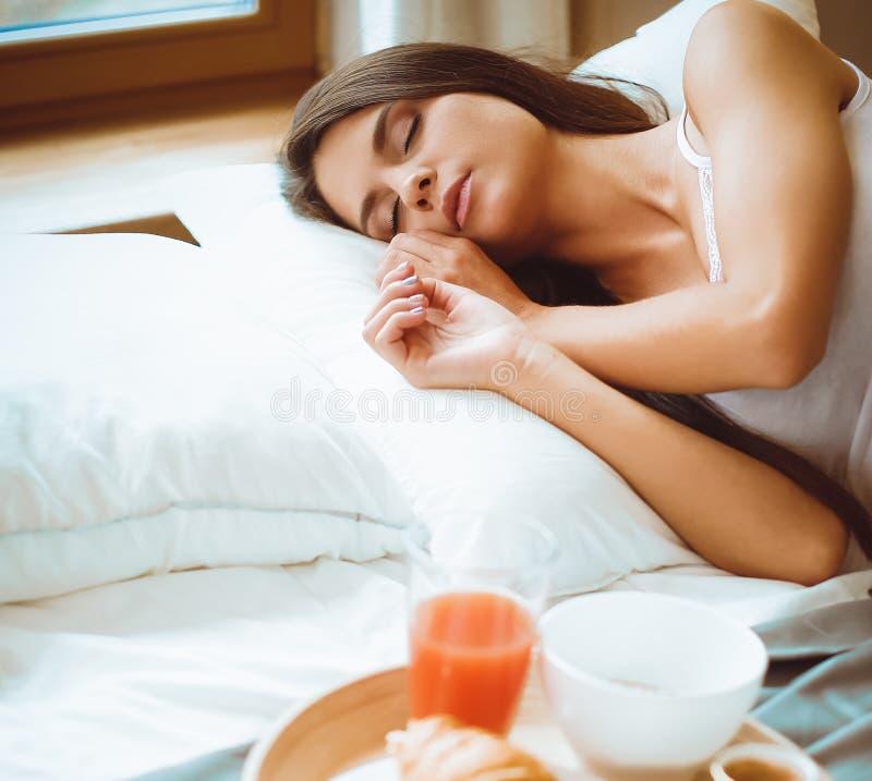Prima colazione a letto con caffè ed il croissant per la giovane donna attraente fotografia stock