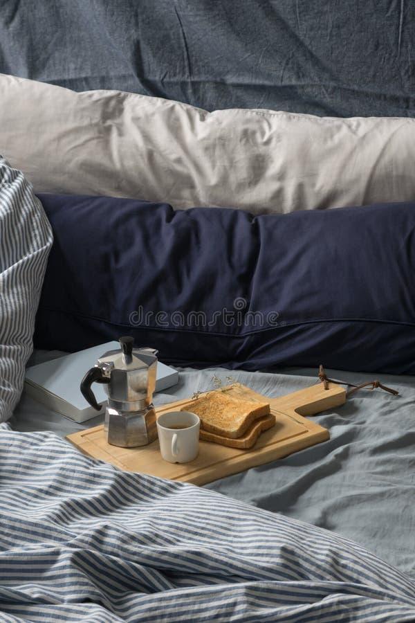 Prima colazione a letto, libro, caffè espresso e pane tostato di mattina fotografie stock