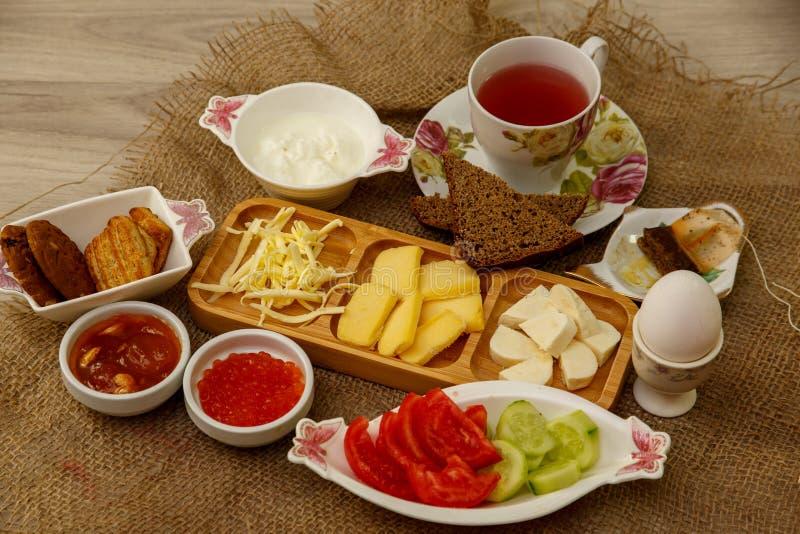 Prima colazione naturale che consiste dei formaggi, del caviale, dei pomodori, dei cetrioli, del burro, delle uova, del pane di s fotografia stock libera da diritti
