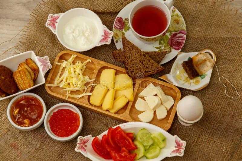 Prima colazione naturale che consiste dei formaggi, del caviale, dei pomodori, dei cetrioli, del burro, delle uova, del pane di s immagini stock